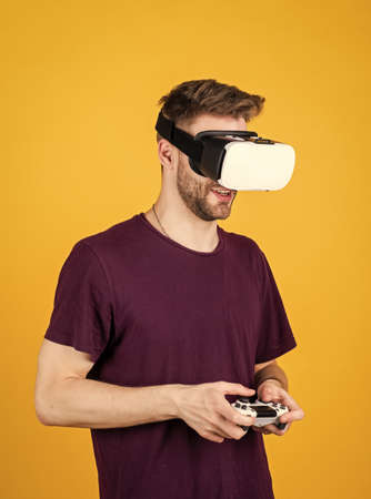 Modern technologies. man wear wireless VR glasses. guy play video games. game player with console. male in VR headset. Happy gamer use modern technology. Digital future and innovation. Visual reality Archivio Fotografico