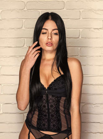 Sexy beautiful girl in lace underclothes. sensual seductive attractive brunette. she is wearing hot lingerie with stockings. Erotic ladies fashion concept. close to orgasm. silicone implants