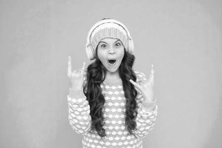 create feel-good playlist. music mood. little child knitted sweater and hat. musical suggestions for winter playlist. her favorite winter songs. surprised girl enjoy winter playlist in headphones