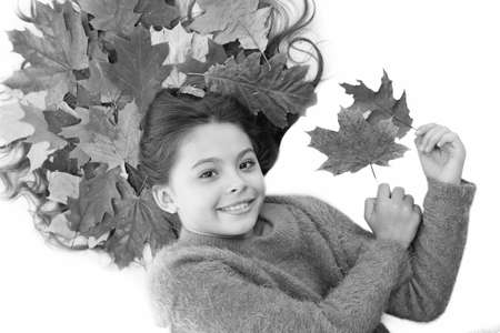 Prevent dry split hair ends. Child enjoy fall season. Girl cute kid long hair lay on white background with fallen leaves. Dry maple leaves in hairstyle. Fall season concept. Hair care in autumn