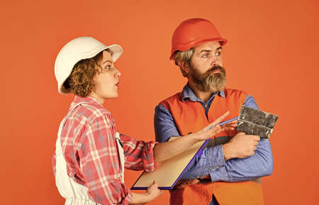thinking couple. renovation and people concept. Builder Couple Look At Home Plans. couple looking at a blueprint. woman and man wear safety hardhat. family standing inside house under construction