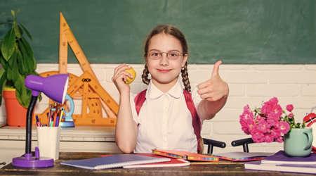 Girl small child eating apple snack. School break. Relax between lessons. School life concept. Healthy lifestyle. Modern childhood. Schoolgirl sit desk chalkboard background. Kid student in school