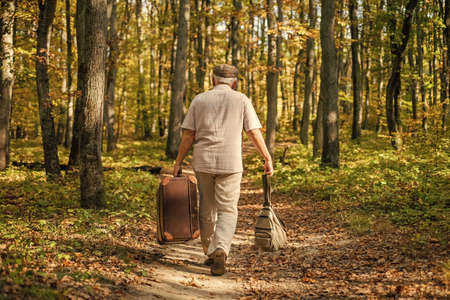 Old man walk with suitcase. retirement concept. Old man carry travel bag in woodland. Elderly person travel through autumn forest. Pleasure travel. Traveling and vacation. Fall season. Idyllic nature