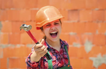 little girl in hard hat holds hammer. best repairer ever. learning to use hammer. hammering. she is good assistant. Kid engineer with carpenter work hammer. selective focus. Labor day at 1 may