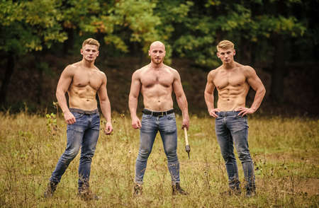 Bandit gang and conflict. relax after work in the forest. three muscular men with axe. athletic man use ax. brutal and strong male. sexy guys six packs and biceps. protein or steroids. bodybuilding Reklamní fotografie