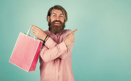 happy bearded man with present pack. cheerful brutal hipster hold gift. paper shopping bag. birthday surprise at party. man with package