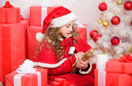 Child write letter to santa claus. Dear santa. Girl hold pen and paper near christmas tree and gift box. Believe in miracle. Send letter for santa. Wish list. Child santa costume enjoy christmas eve
