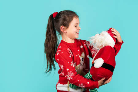 Dear Santa. Small kid carry Santa toy blue background. Little girl toy present. Winter holidays. Gift brings joy and happiness. Merry christmas. Christmas vibes concept. Christmas traditions