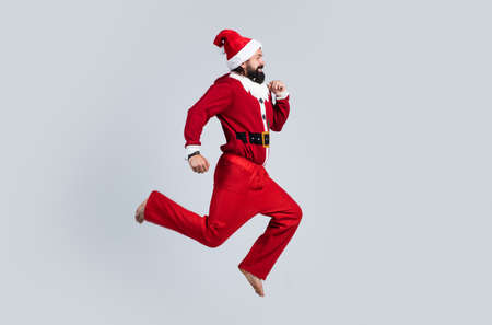 happy bearded hipster in red santa claus costume running and feel happiness about christmas shopping sales, new year party