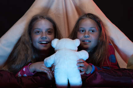 Kids wearing red jammies holding white teddy bear in bed Archivio Fotografico