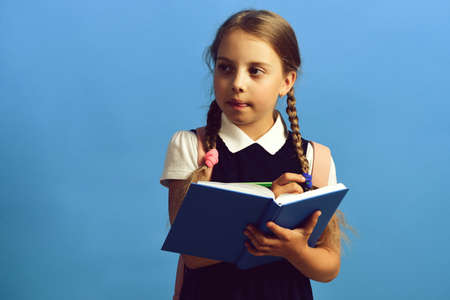 Girl writes in big blue notebook. Pupil in school uniform 免版税图像