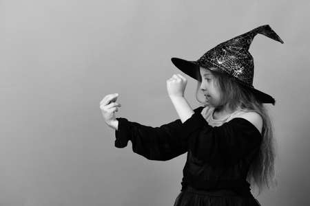 Kid in witch hat, dress and concentrated face