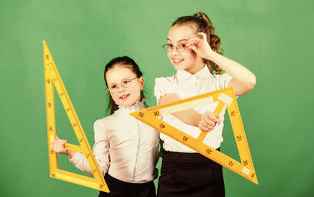School students learning geometry. Pupil cute girls with big rulers. small girls back to school. STEM school disciplines. math lesson. Education and knowledge. high school