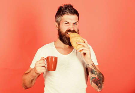 feel hunger. Bearded hipster enjoy breakfast drink coffee. Morning tradition concept. Fresh baked croissant. Delicious breakfast. Unhealthy but yummy breakfast. Perfect match