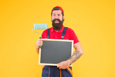 Ready to work. creative idea. foreman advertises the service of wall facing. happy man with board copy space. mature hipster use paint roller tool for painting. repairman or builder working