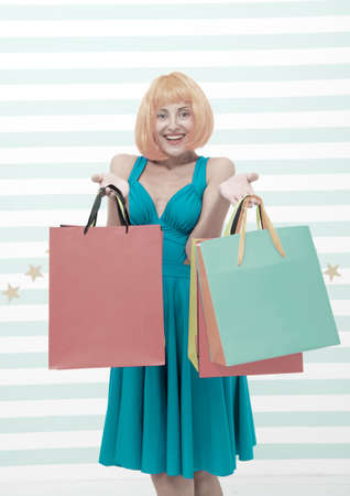 crazy girl shopping. happy woman with orange hair hold purchase. girl with shop bags after big sale on cyber monday. benefit concept. crazy about shopping. shopaholic woman