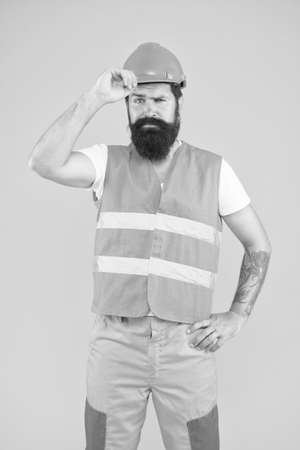 Responsibility. Man protective hard hat and uniform. Worker brutal bearded builder confident looking camera. Protective equipment concept. Strong handsome builder. Indoors works. Dangerous works