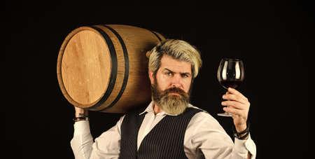 Sommelier at work. Bearded businessman in elegant suit with barrel. Sommelier tastes expensive drink. Elegant waiter carry wine. working in wine cellar. Wine bar or winery. wine degustation