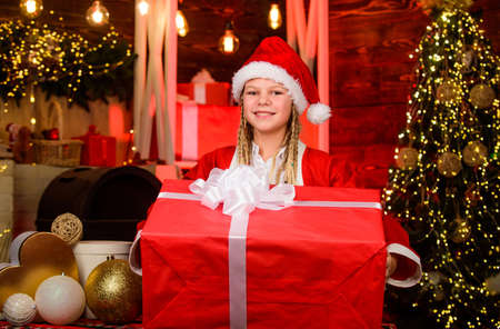 Child having fun on christmas eve. Happiness and joy. Girl Santa claus costume received gift. Santa crew. Santa party. Happy new year. Giant enormous surprise. Winter masquerade. Generous holiday Archivio Fotografico