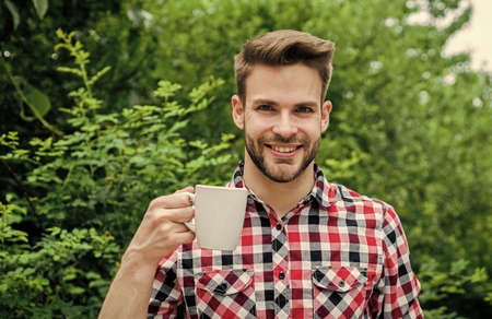 More coffee. fresh inspiration and energetic beverage. handsome bearded guy drinking tea outdoor. he loves cocoa. food and drink. cheerful man in checkered shirt drink morning coffee. good morning