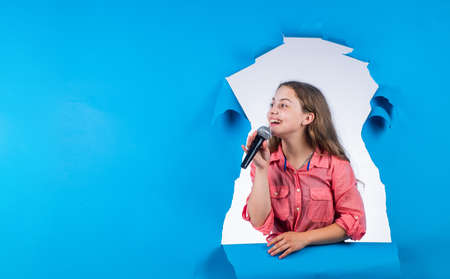 make your voice louder. teen girl singing song with microphone. having a party. Happy kid with microphone. karaoke concept. Singing Songs. Lifestyle and People Concept. copy space