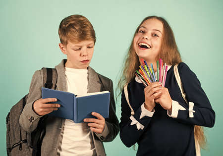 We are writing our future. Happy boy and girl hold pens and copybook. Little children learn reading and writing at school. Learning writing skills in primary school. Improving calligraphic writing