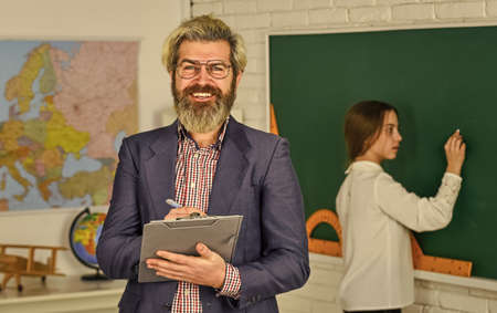 bearded man make notes in clipboard. little girl write answer on blackboard. exam or lesson. back to school. modern education concept. teacher and child in classroom. change of duties Reklamní fotografie