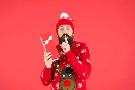 keep a secret. xmas shopping time. prepare gifts and presents. bearded man in santa hat. happy new year party fun. celebrate winter holidays. merry christmas. man in funny knitted sweater with box 版權商用圖片