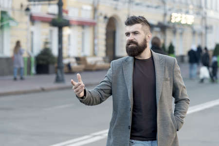Happy to meet you. Hipster in casual coat happy to meet friend at urban street. Chance meeting concept. Meet old friend by accident. Man bearded businessman waiting someone in city center