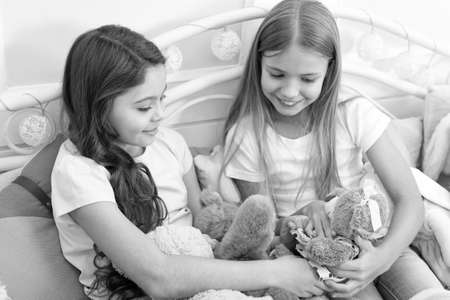 Pajamas party. Sisters sharing toys. Sisters best friends. Kids play toys in bed. Little girls spend time together. Friendship personal relations. Toys shop. Cute soft toys. Happy childhood Stock Photo