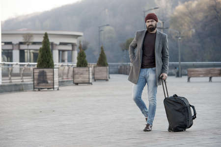 Hipster ready enjoy travel. Looking for accommodation. Man bearded hipster travel with big luggage bag wait for taxi bring him to hotel. Travel tips. Traveler with suitcase arrive travel destination