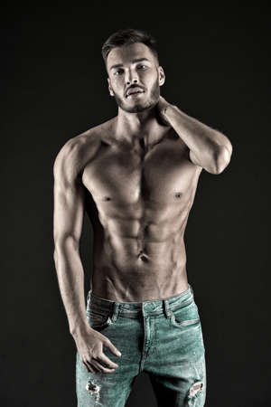 Check out my shape. Man muscular torso tense muscles veins denim pants. Macho muscular chest looks attractive black background. Athlete with muscular body on confident face proud of his shape
