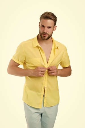 Handsome macho fashion model. Sexy macho shopping clothes. Hot day. Heat season. Modern fashion. Dressing room. Attractive man taking off shirt. Confident in his appealing. Bearded guy casual style