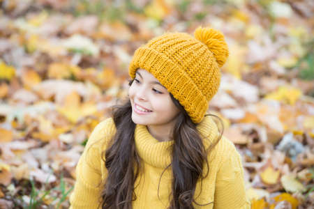 happy child in casual style spend time in autumn park enjoying good weather wearing knitted hat and warm sweater, fashion