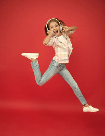 Jumping mid air. Happy small girl dancing. Cute child enjoying happy dance music. Music is happiness for her. Easy listening music. Small girl listening to music in headphones. Dancing girl