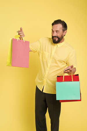 Shop and enjoy. Shopping addict yellow background. Mature man hold shopping bags. Happy shopper with paperbags. Sale and shopping. Shopping as it should be, copy space