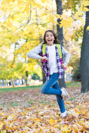 Energetic little kid carry backpack running to school in autumn park outdoors, September 1