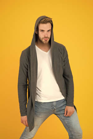 Casual menswear. Freedom of movement. Fashion trends. Modern clothes for youth. Sporty style. Fashion man yellow background. Fashion look. Handsome guy wear fashionable mantle with hood