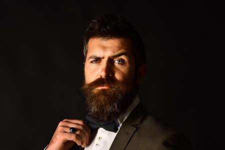 Businessman with confident face adjusts bow tie 免版税图像