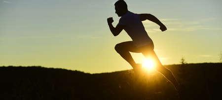 Silhouette of athlete running on sunset background, copy space. Standard-Bild