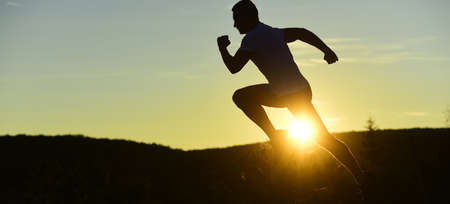 Silhouette of athlete running on sunset background, copy space. Stock Photo