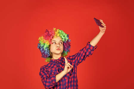 kid looking funny in rainbow wig hair. hair dyeing at hairdresser. child having fun. happy birthday party. small girl colorful wig make selfie on phone. positive and cheerful. childhood happiness