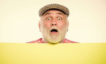 Event announcement. Pensioner grandfather in vintage hat poster information copy space. Elderly person. Announcement concept. Senior bearded emotional man peek out of banner place announcement