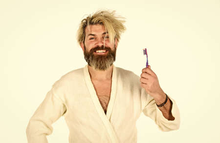 relaxed man in white terry bathrobe. Morning portrait of bearded man. man spend day off at home. carefree guy hold tooth brush. health and hygiene. handsome man brush teeth in morning Zdjęcie Seryjne