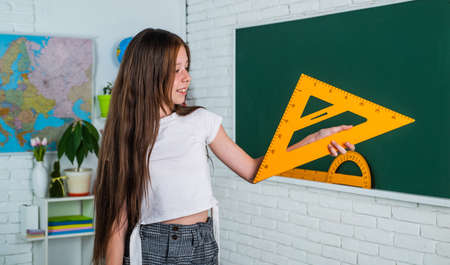 teen girl work in classroom with math tools. cheerful kid learning mathematics subject. modern education. knowledge day. child pupil hold triangle ruler. girl is college student. back to school Standard-Bild