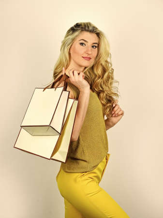 sexy blonde carry shopping bags. elegant woman shopaholic. girl shopper hold paperbag package. buy presents online. gift shop for any holiday. sell-out on black friday. nice purchase