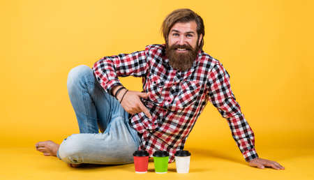lifestyle concept. handsome hipster man with cup of take away coffee. he is taking coffee break. Handsome mature guy drinking from cup. Hold paper cup of coffee or tea