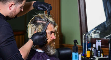 mature man at hairdresser. Hair care and male grooming concept. get perfect shape. bearded man getting beard haircut by barber. moustache and beard. sitting in chair at hairdresser Banco de Imagens
