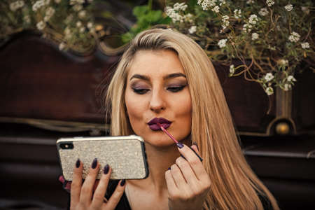 Hair like fire. blonde beauty use phone as mirror. makeup tutorial fashion blog. lady put lipstick on lips. cosmetics and makeup. follow my fashion. prepare for date meeting. always looking good