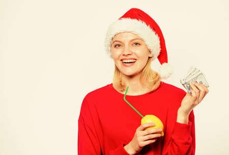 Symbol of wealth and richness. Rich girl with lemon and money. Girl santa hat drink juice lemon while hold pile money. Make money on fresh lemonade. Christmas profit concept. Lemon money concept